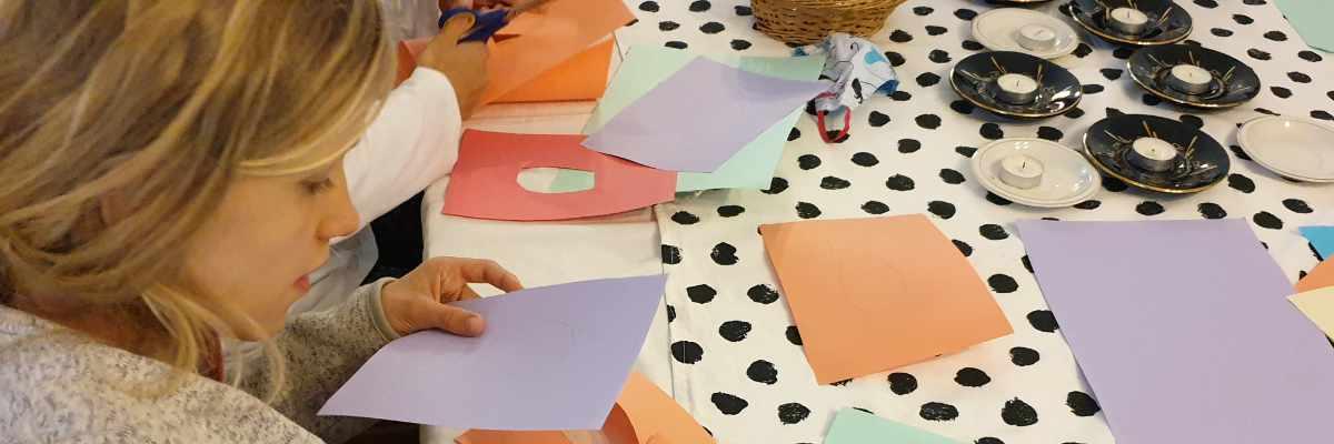 Náhledový proužek nedělní besídky. Holčička stříhá fialový kousek papíru.